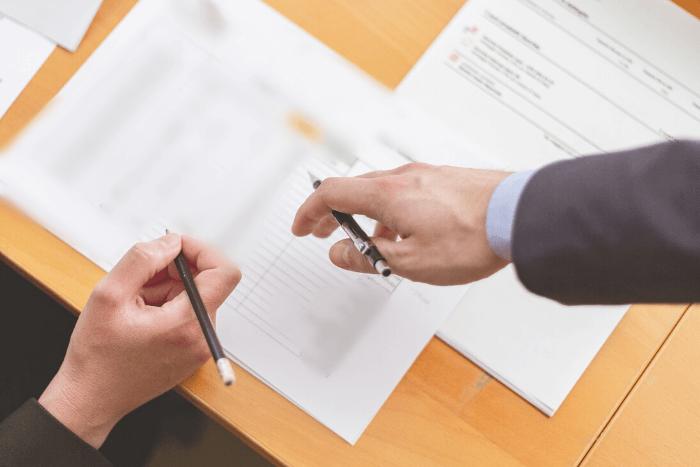 εργαζόμενος και εργοδότης που ετοιμάζονται να υπογράψουν χαρτιά