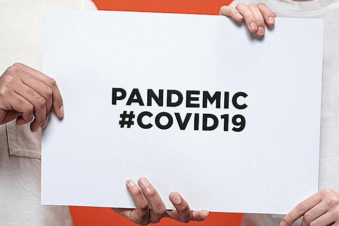 """Πλακάτ με τη φράση """"Pandemic #covid19"""" το κρατάνε ένας άντρας και μια γυναίκα"""