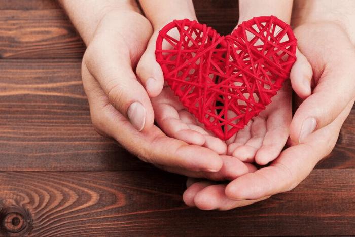 γονιός με παιδί κρατούν κόκκινο αντικείμενο σε σχήμα καρδιάς