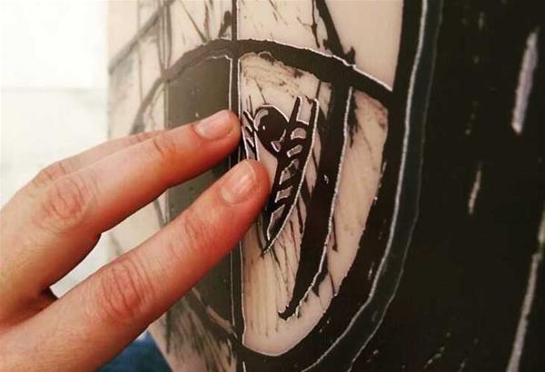 χέρια που αγγίζουν έργο με ανάγλυφη εκτύπωση πάνω σε πλέξι γκλας