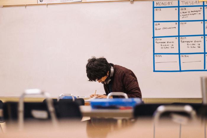 μαθητής μόνος του σε αίθουσα γράφει