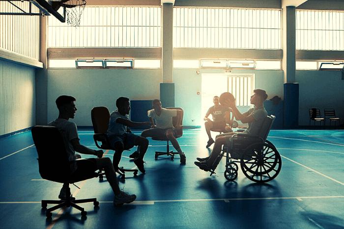 στιγμιότυπο από την ταινία ο πρωταγωνιστής στο αμαξίδιο και οι φίλοι σε καρέκλες με ροδάκια παίζουν μπάσκετ