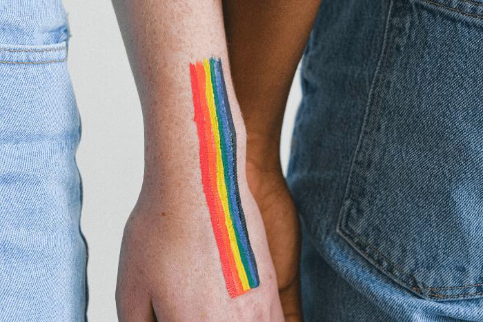 δύο άτομα που κρατιούνται από τα χέρια και έχει χρωματισμένο το σήμα των ΛΟΑΤ το ένα χέρι