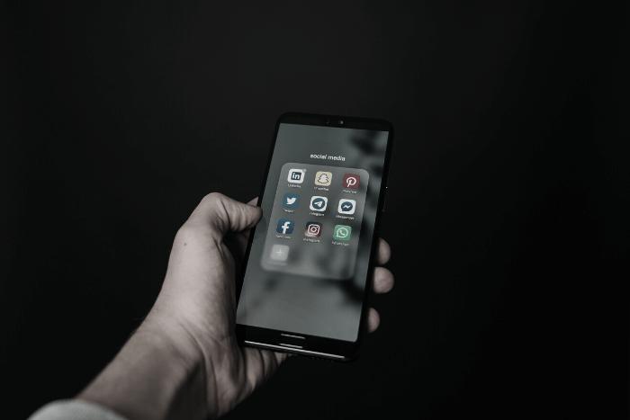 χέρι που κρατάει κινητό με social media