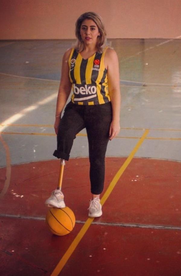 η Νεσρίν Ακιούζ σε γήπεδο του μπάσκετ, κρατάει μπάλα με το πρόσθετο μέλος