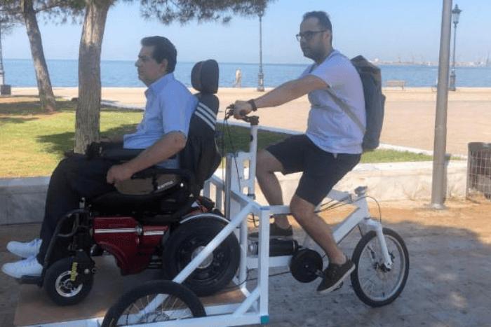 κοινόχρηστο ποδήλατο μπροστά άτομο με αμαξίδιο πίσω συνοδός