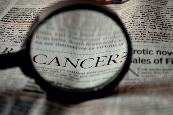 Η λέξη cancer μέσα από μεγεθυντικό φακό σε εφημερίδα