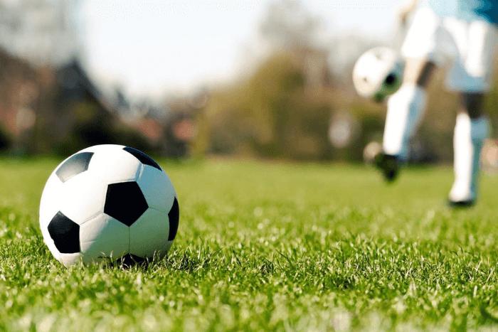 Μπάλα ποδοσφαίρου σε πρώτο πλάνο και ποδοσφαιρστής πιο πίσω