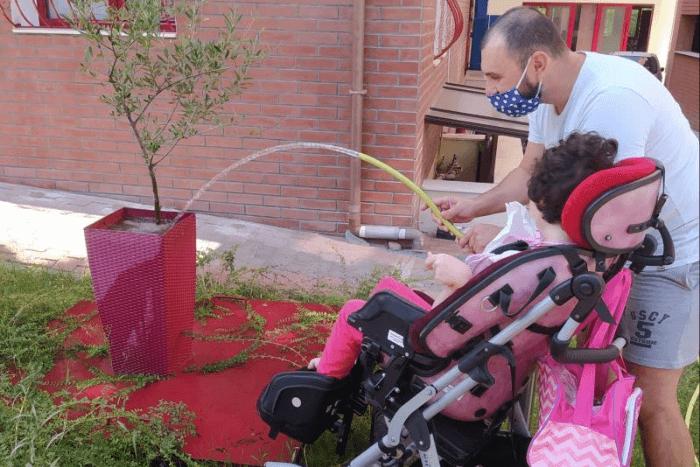 παιδί με αναπηρία που με τη βοήθεια ενηλίκου ποτίζει γλάστρα