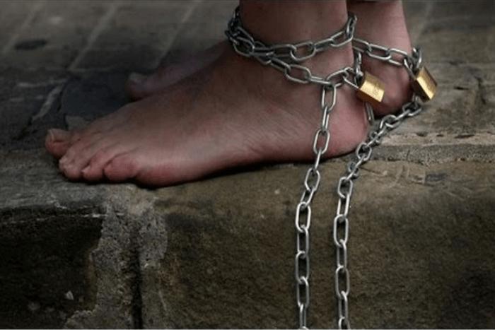 άνθρωπος που έχει στα πόδια του αλυσίδες με λουκέτα