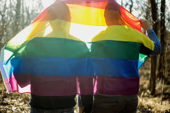 Πρόσφυγες γυρισμένοι πλάτη με σημαία ΛΟΑΤΚΙ στα κεφάλια τους