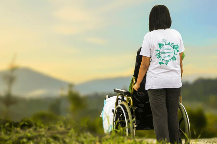 Κοπέλα πλάτη που κινεί αναπηρικό αμαξίδιο