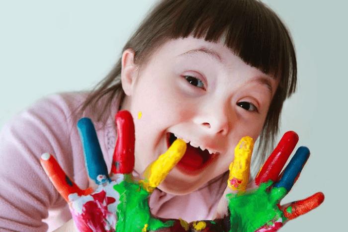 Κορίτσι με Σύνδρομο down με χέρια χρωματιστά από μπογιές