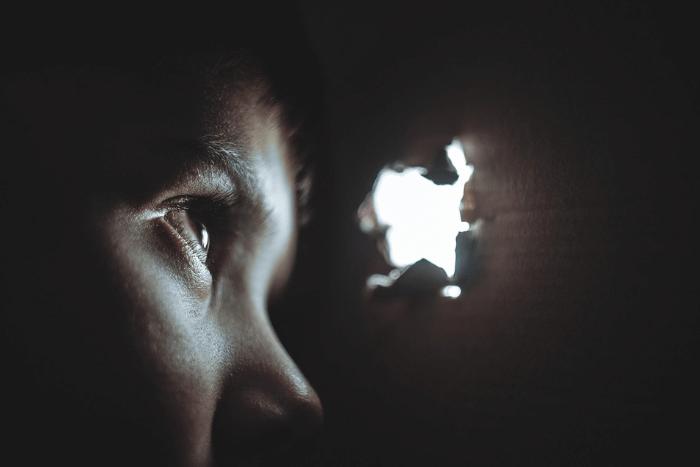 άτομο που κοιτάει μέσα από μια τρύπα τον κόσμο έξω
