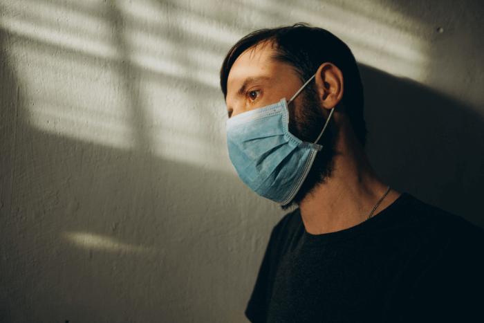 άντρας με μάσκα μέσα σε σπίτι κοιτάει έξω από το παράθυρο