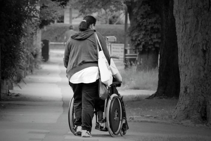 Γυναίκα που κινεί αναπηρικό αμαξίδιο