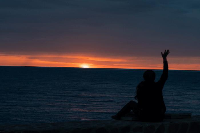 φιγούρα κοπέλας πλάτη σε εμάς κοιτάει τη θάλασσα και ηλιοβασίλεμα. έχει το χέρι ψηλά και χαιρετάει