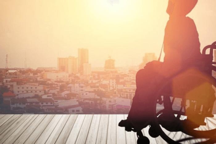 άτομο αμαξίδιο βλέπει μια πόλη από ψηλά και το φως του ήλιου πέφτει πάνω του