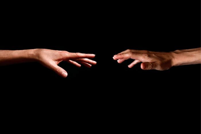δύο χέρια που προσπαθούν να ακουμπήσουν το ένα το άλλο