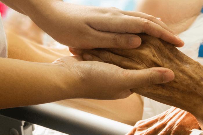 Χέρια νέου ατόμου κρατάνε χέρια ηλικιωμένου ατόμου