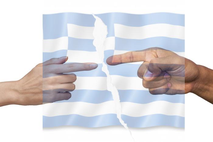 Ελληνική σημαία κομμένη στα δύο και δύο δάχτυλα ανδρός και γυναικός που δείχνει ο ένας τον άλλον