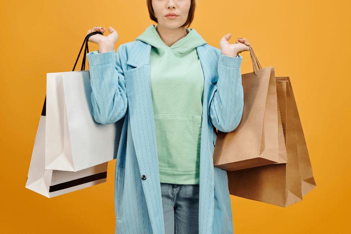 Γυναίκα που κρατάει τσάντες με ψώνια και στα δύο χέρια της