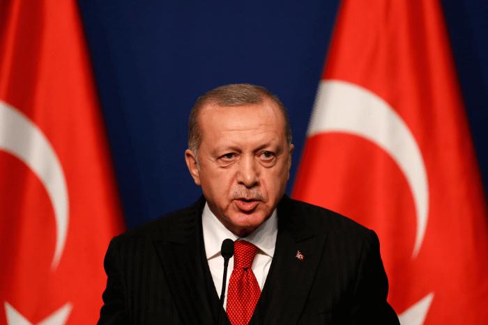 Ο Ταγιπ Ερτογάν με δύο σημαίες της Τουρκίας δεξιά και αριστερά του