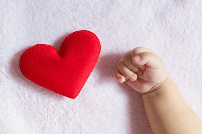 Χέρι μωρού δίπλα σε καρδιά