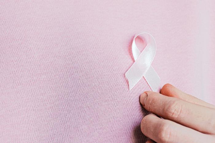 γυναικείο χέρι που κρατάει ροζ κορδέλα στο σημείο του στήθους