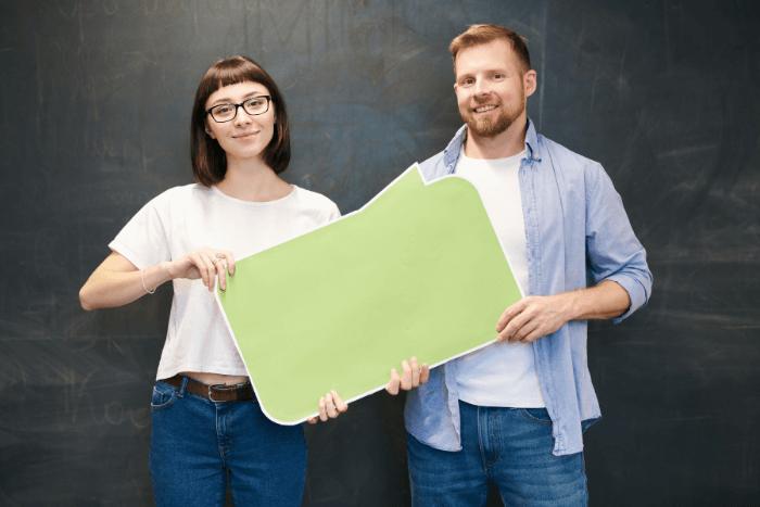 Γυναίκα και άνδρας που κρατάνε ένα πράσινο χαρτόνι και οι δύο μαζί