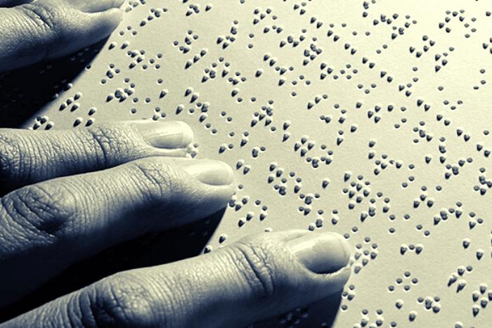 Χέρια που διαβάζουν σελίδα braille