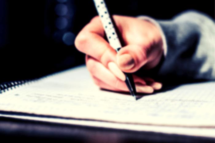 χέρι που γράφει σε τετράδιο