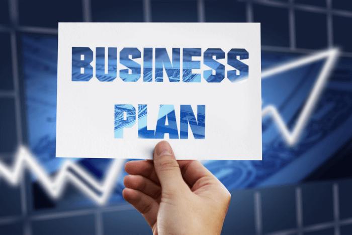 """χέρι που κρατάει χαρτί που γράφει """"Business Plan"""""""
