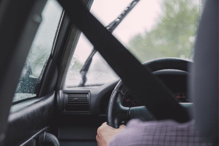 άνθρωπος σε αυτοκίνητο οδηγεί. Φωτογραφία τραβηγμένη από πίσω φαίνεται χέρι στο τιμόνι και φορεμένη ζώνη ασφαλείας