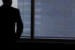 Άνδρας με κουστούμι που βλέπει έξω από παράθυρο. Εμείς βλέπουμε την πλάτη του.