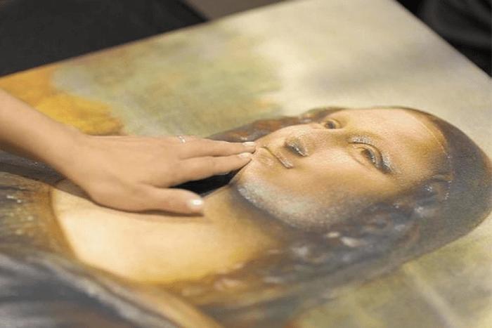 """χέρια που αγγίζουν το έργο του Λεονάρντο Ντα Βίντσι """"Μόνα Λίζα"""""""