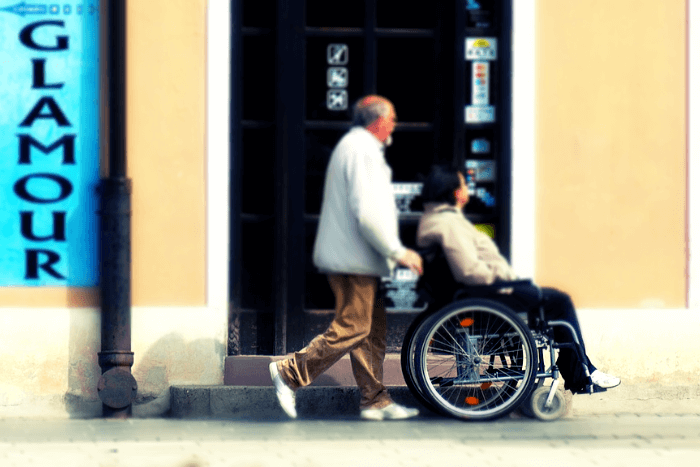 άνδρας κινεί γυναίκα που βρίσκεται σε αναπηρικό αμαξίδιο