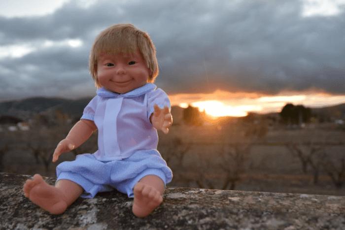 Κούκλα με σύνδρομο down κάθεται σε εξωτερικό χώρο πάνω σε μάντρα πίσω ηλιοβασίλεμα