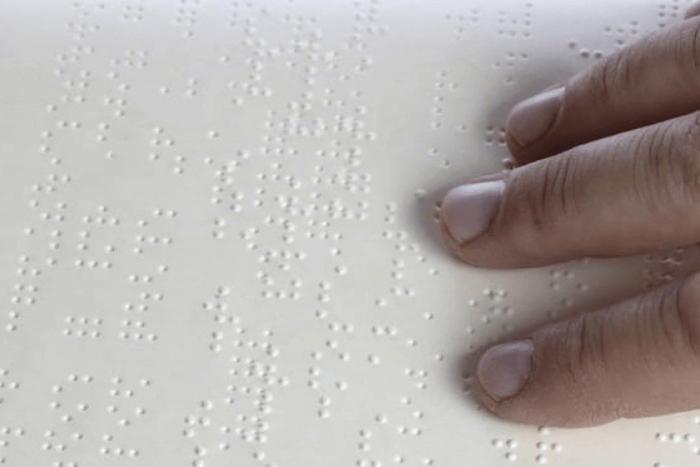 χέρια πάνω σε γραφή braille