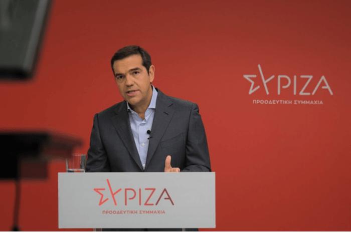 Αλέξης Τσίπρας σε κόκκινο φόντο με το λογότυπο του ΣΥΡΙΖΑ