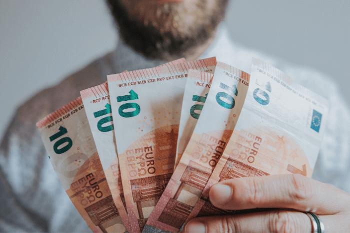 Άνδρας που κρατάει χαρτονομίσματα τον 10€ στα χέρια