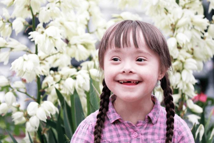 κορίτσι με σύνδρομο down και πίσω του κήπος με λουλούδια