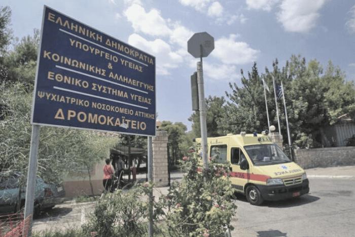 Δρομοκαϊτειο εξωτερική είσοδος κτιρίου, ταμπέλα νοσοκομείου και ένα ασθενοφόρο να φεύγει