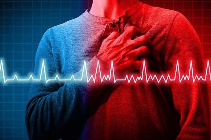 Άνδρας που κρατάει με το ένα του χέρι την καρδιά του. Στη μέση της φωτογραφίας υπάρχει η γραμμή του καρδιογραφήματος