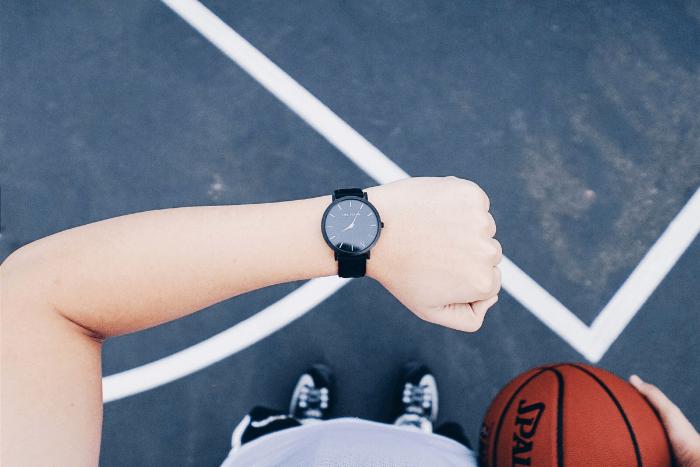 Άτομο που κρατάει μπάλα του μπάσκετ σε γήπεδο και ταυτόχρονα κοιτάει το ρολόι του