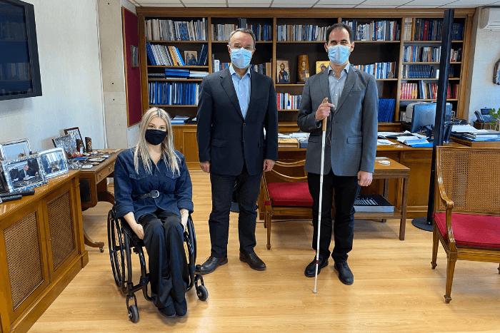 """Ο Υπουργός Οικονομικών Χρήστος Σταϊκούρας με τους εκπροσώπους της ΑΜΚΕ """"Με Άλλα Μάτια"""": τον ιδρυτή, τυφλό δικηγόρο Βαγγέλη Αυγουλά και την εργαζόμενη στην ΑΜΚΕ Δήμητρα Κονοτβά (κινητική αναπηρία) στο Γραφείο του Υπουργού."""