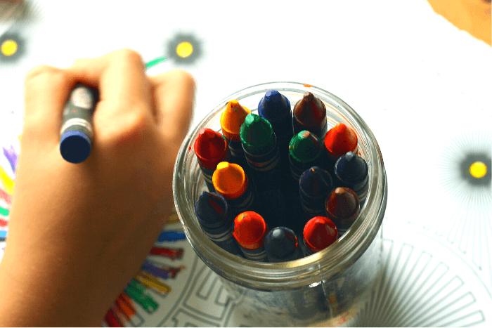 χέρι παιδιού που ζωγραφίζει ένα σχέδιο και δίπλα του βαζάκι με κηρομπογιές