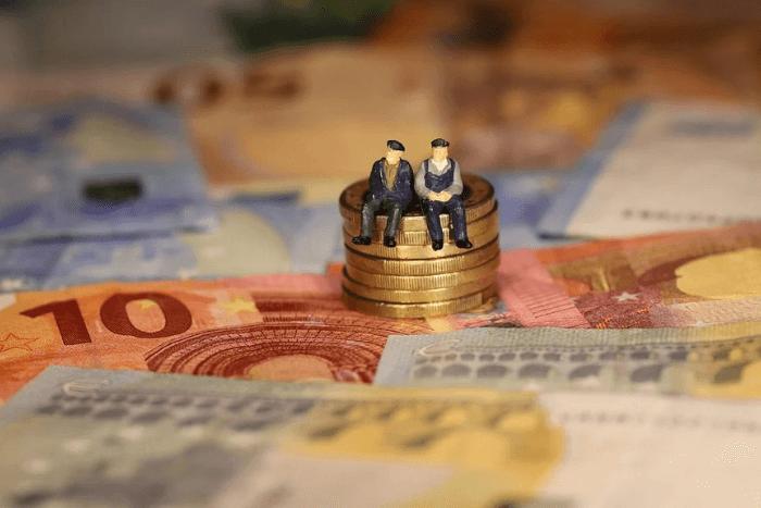 χαρτονομίσματα ευρώ και μια στίβα κέρματα ευρώ που πάνω κάθονται δύο ανθρωάκια
