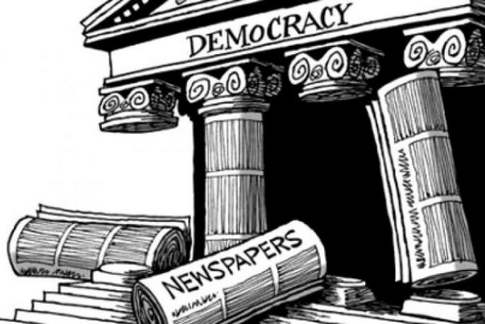 """Σκίτσο: Αρχαίος Ναός που γράφει """"Democracy"""" με σπασμένους κίονες και μπροστά από το Ναό """"εφημερίδες"""