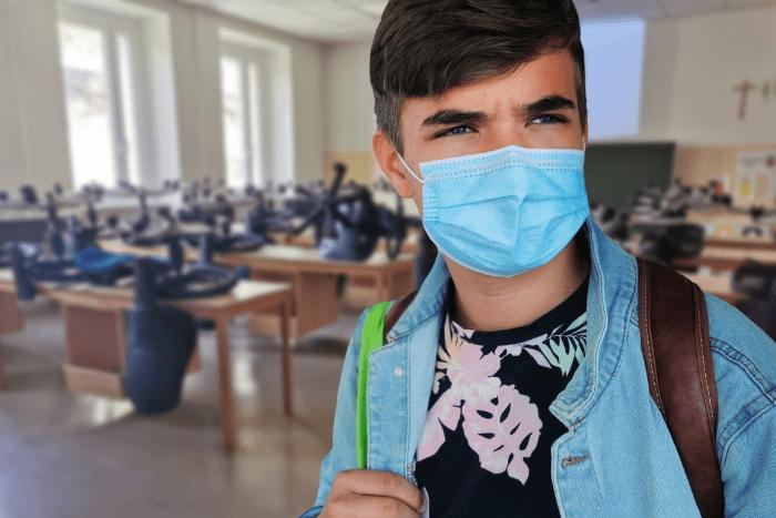 Μαθητής με μάσκα και πίσω του αίθουσα που δεν λειτουργεί με καρέκλες πάνω σε θρανία